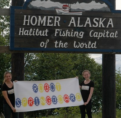 Hannah Tipperman and Rachael Tipperman co-founders of Robot Springboard holding sign in Homer Alaska site of first robotics camp for children